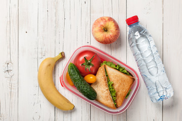 Lunch box with sandwich and tomatoes, water bottle, apple, banana