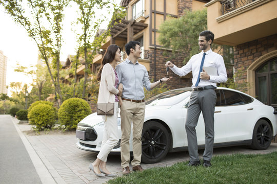 Happy young couple receiving car key from car salesperson