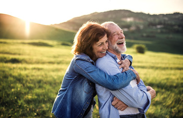 Side view of senior couple hugging outside in spring nature at sunset. Fototapete