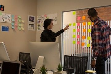 Business colleagues discussing over sticky notes