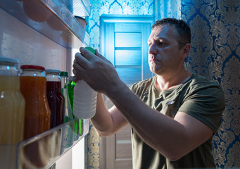 Man selecting something to drink from a fridge