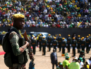 An armed soldier stands as Zimbabwe's President Elect Emmerson Mnangagwa addresses the people gathered at the national 38th Heroes Day Commemorations at the Heroes Acre in Harare