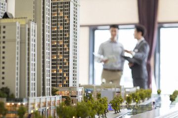 Realtor showing architectural model to young man