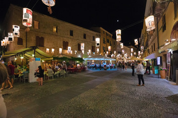 Night view of the historic center with the bustling city life of the city of Alghero in Sardinia, Italy.