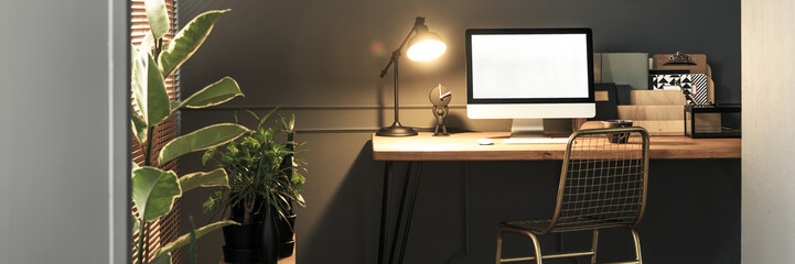 Creative golden, metal chair by a wooden desk with computer screen, folders and an industrial luminous lamp in a stylish home office interior