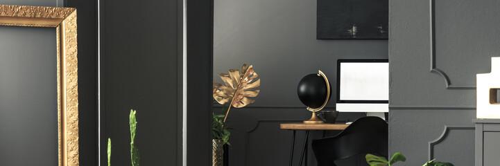 Golden decorations in a chic living room interior with gray walls and a computer screen on a wooden desk in the workplace area