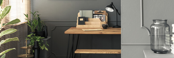 Organized folders and notebooks on a wooden desk with a black, industrial lamp - a creative study space in a gray, fancy apartment interior with plants
