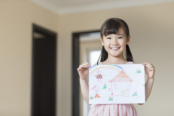 Cute little girl showing her drawing of new house