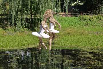 """A ballerina made of cloth over a pond in the botanical garden """"Aptekarskiy Ogorod"""" in Moscow, Russia"""