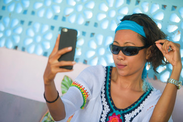 young happy and attractive Southeast Asian Indonesian woman taking selfie photo portrait with mobile phone camera posing cheerful and playful