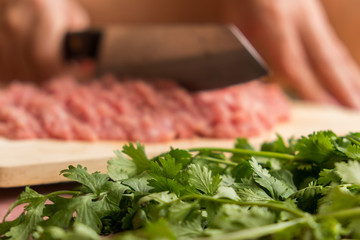 Chef is chopping the raw pork on the wooden cutting board with a sharp knife to cook in the kitchen.