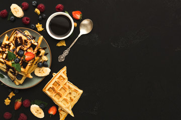 Waffles with fruits, breakfast background top view on black