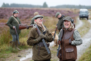 Members of a shooting party on Forneth Moor laugh before they set off on the opening day of the grouse shooting season, Scotland