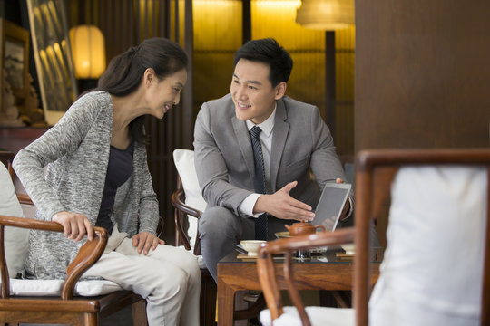 Confident financial consultant talking with a mature woman