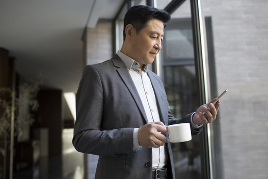 Businessman using smartphone while having coffee in office