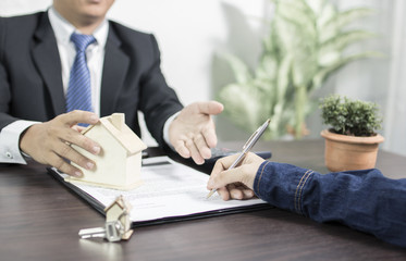Bank agency explaining to home loan people and buyer signing on home and estate purchase contract, house buying concept