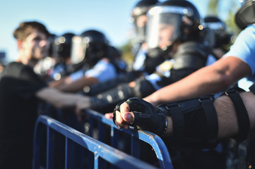 Security staff hands on a protection fence during a riot