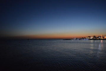 Beautiful sea water with reflection and the embankment of the Black Sea, houses with bright lanterns at sunset at sunset