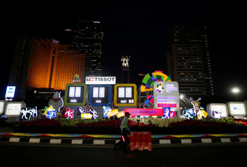A worker from TransJakarta bus system pushes a road divider near a countdown clock for the upcoming 18th Asian Games in Jakarta