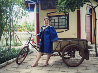A Charming Asian Girl / Lady in The Blue, Chinese Style Academic Dress or Graduation Gown in A Public Park of CHINA.