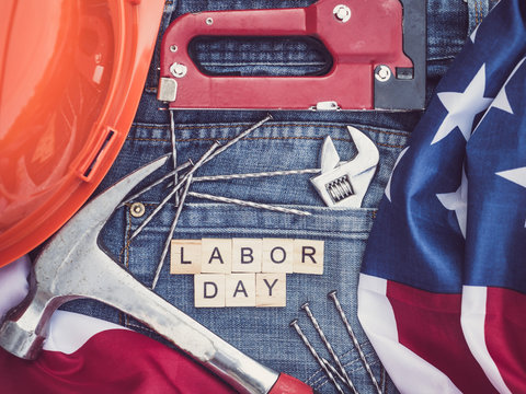 Wrench, staple gun, steel nails and wooden letters with the inscription LABOR DAY on the background of a blue jeans pocket. Top view, close-up. Preparing for the celebration of Labor Day