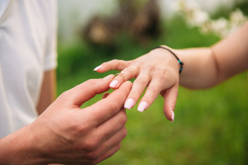 Man makes a marrige proposal to a girl. Gives her a ring for the engagement. Close-up hands