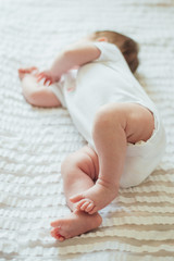 Cute infant child sleeping on white sheets