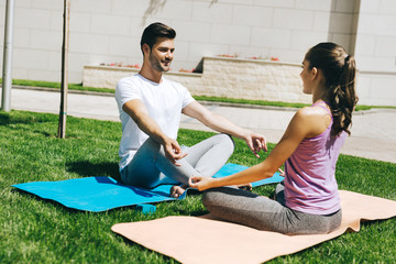 For body and mind. Delighted nice couple smiling while enjoying yoga together