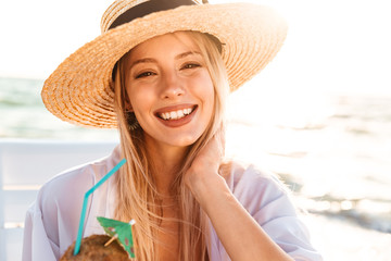Photo of happy young woman 20s in summer straw hat laughing, and drinking cocktail during sunrise at seaside
