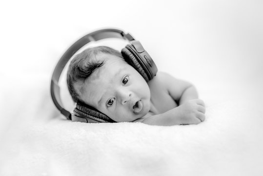 Cute newborn baby hearing music with headphones on a blanket - happy family moments