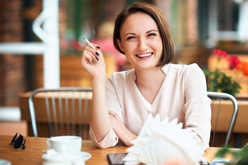 Young woman smokes tobacco in a cafe