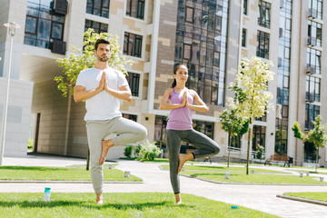 Yoga pose. Positive healthy people standing on one leg while practicing yoga