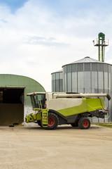 grain pile and a combine near a granary and silos