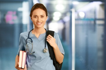 Young female doctor on blurred hospital background