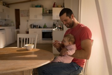Father feeding his baby boy with spoon