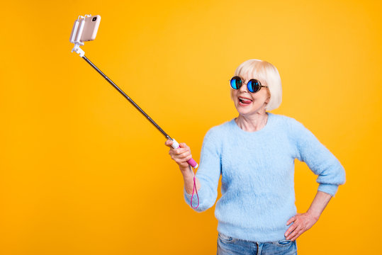 Young soul grandmother making selfie to the front camera isolate