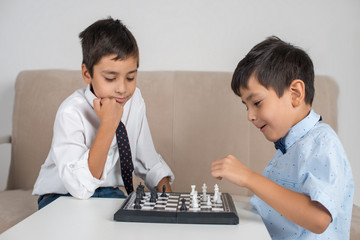 Schoolboys  wearing  shirts with ties are enthusiastically playing checkers or chess