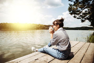 young adult woman sitting on wooden dock drinking coffee and loo