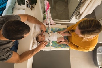 Overhead view of father and mother changing diaper of their baby boy