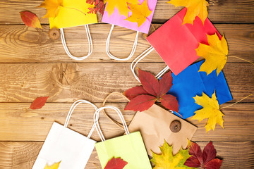 Color shopping paper bags and autumn leaves, flat lay, copy space. Autumn shopping, sales concept. Autumn holiday. Shopping in autumn.