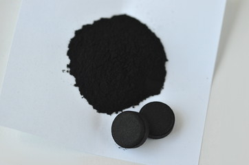 Top view of cosmetic black powdered activated charcoal and beauty face mask mixture in a bowl with copy space on white.