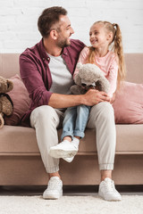 daughter holding teddy bear on father knees and looking at each other