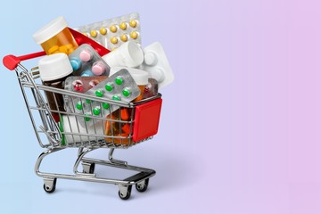 Shopping Cart with pills on background