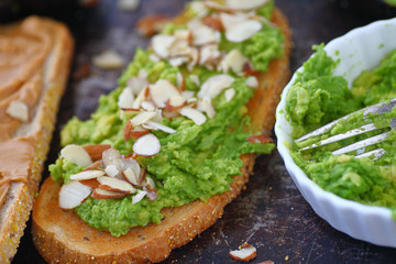 Mashed avocado and sliced almonds on rye bread