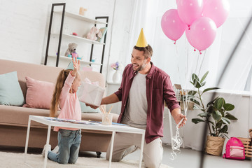 father with pink balloons and gift having fun with daughter