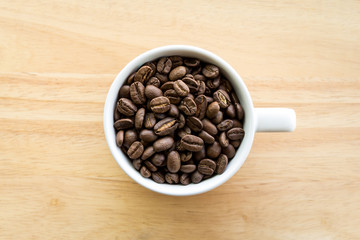 White coffee cup full of coffee beans on wooden background