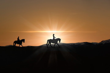 Silhouette of man and woman riding horse across horizon as the sun goes down