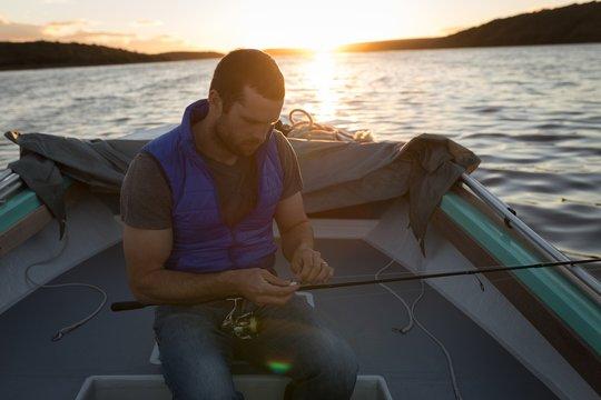 Man tying fishing rod in motorboat