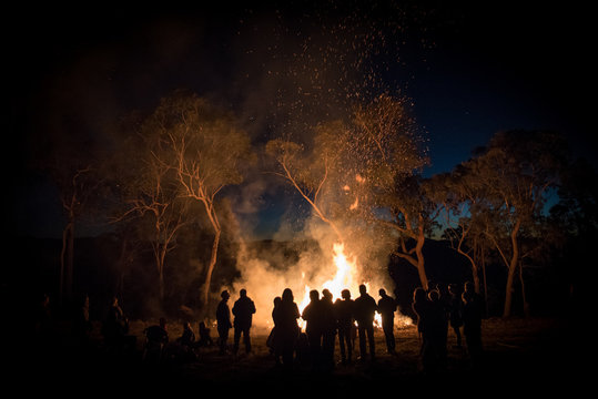 A large group of people gathering around a bonfire