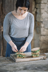 Woman making sandwich on cutting board at home